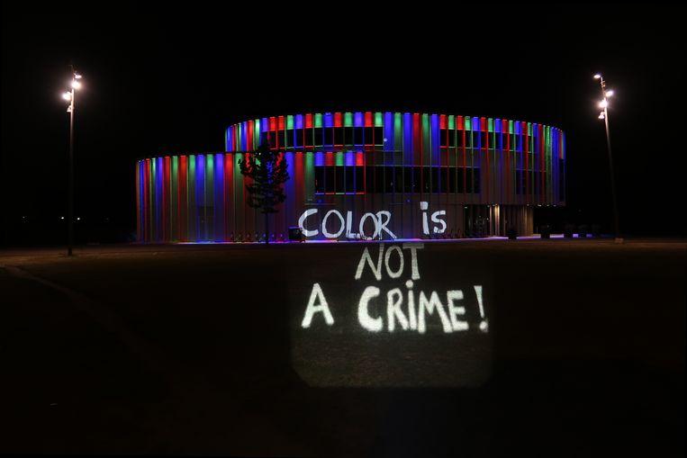 Een van de protestborden wordt uitgelicht op het Bijlmerpark Theater. Beeld Remco Keepers
