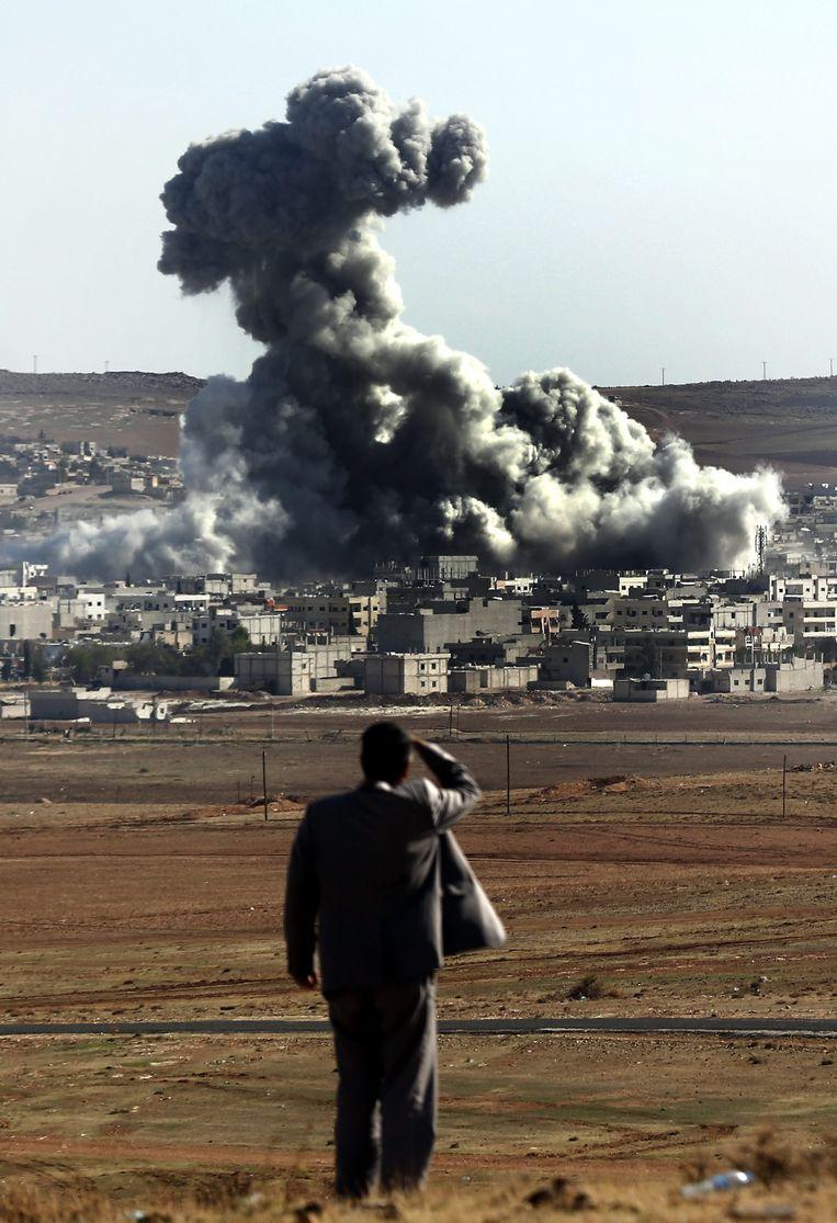 Een man kijkt naar het door de VS geleide bombardement op Kobani. Beeld EPA