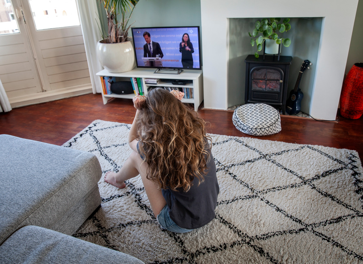 Een tiener zit in spanning te luisteren naar een persconferentie van minister Rutte eerder dit jaar.