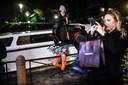 Een vrouw staat op een hekje in Venetië om geen natte voeten te krijgen, terwijl een andere dame een foto maakt.