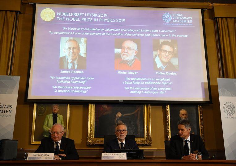 Het Nobelcomité, met op de achtergrond de drie winnaars.  Beeld AFP