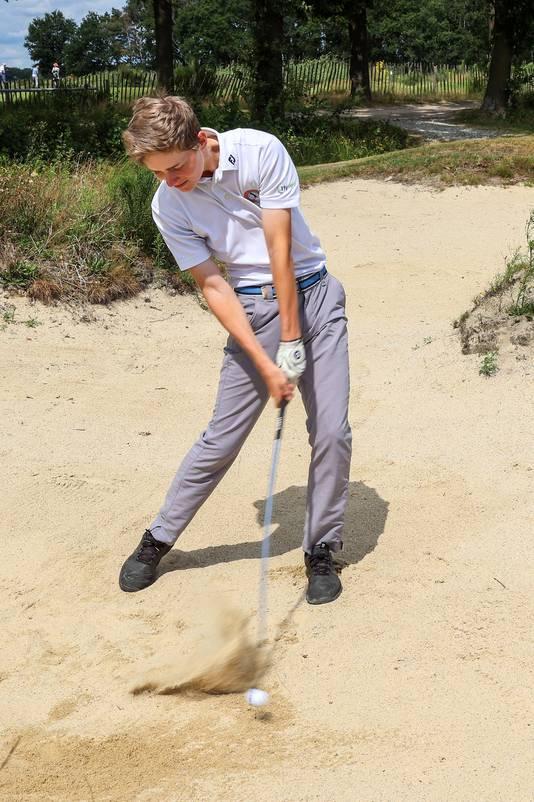 Melvin Muller tijdens een bunkershot op de golfbaan in Bakel die hij op z'n duimpje kent.
