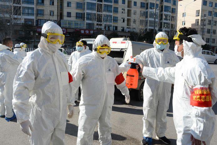 Beeld ter illustratie. Leden van een sanitair team van de politie in beschermde pakken, vlak voor ze verschillende straten in een Chinese stad besproeien met ontsmettingsmiddel in een poging de verdere verspreiding van het nieuwe coronavirus tegen te gaan.