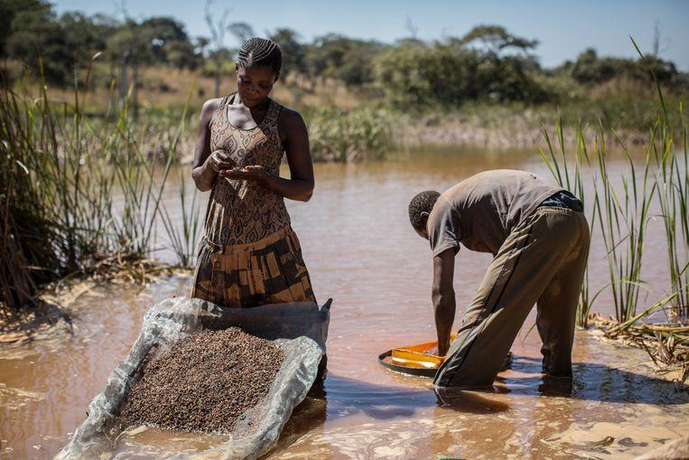 Een vrouw zoekt kobalt tussen de modder en rotsen nabij een mijn in Kolwezi, Congo. Beeld AFP