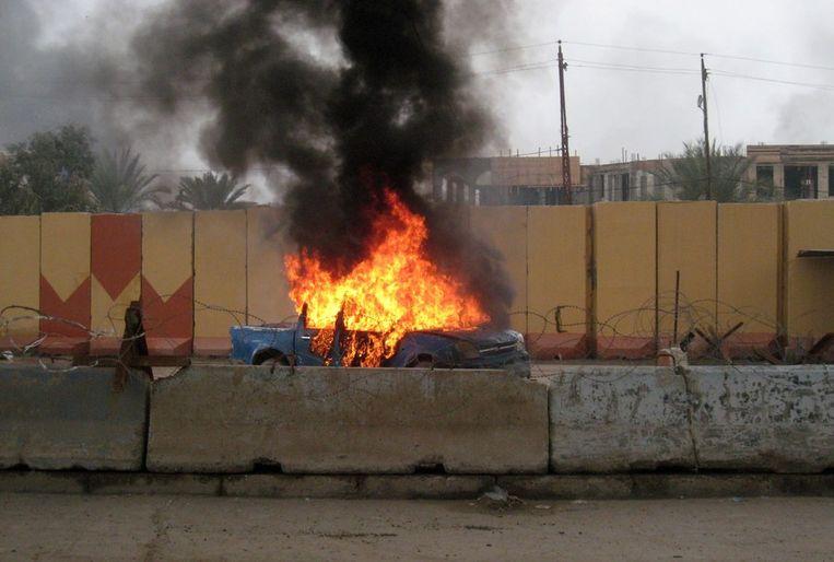 Een brandende politieauto in de Iraakse stad Falluja tijdens de bestorming van de politiebureaus twee dagen geleden Beeld afp