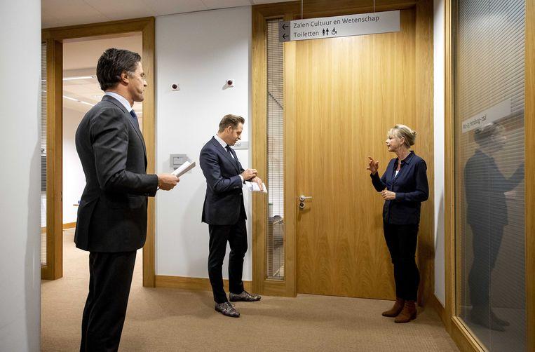 Demissionair premier Rutte en demissionair minister van volksgezondheid Hugo de Jonge kort voordat zij dinsdagavond aan hun persconferentie over de coronamaatregelen beginnen. Rechts gebarentolk Corline Koolhof. Beeld EPA