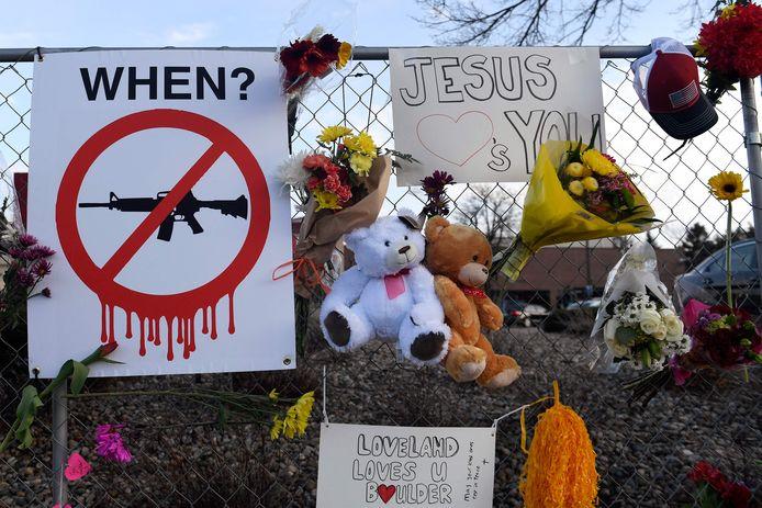 Een affiche tegen aanvalswapens hangt tussen herdenkingssymbolen aan de supermarkt in Boulder in de Amerikaanse stad Colorado waar een jongeman in maart 10 mensen doodschoot.