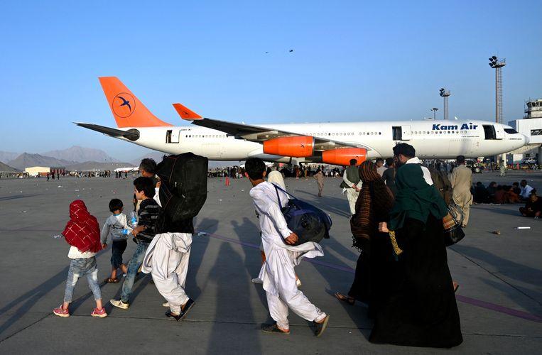 Een Afghaanse familie op het vliegveld van Kaboel. Beeld AFP