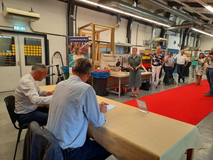 Jos Rijk van De Zuidhoek (l) en Johan van der Elzen van de Start Foundation ondertekenen het contract voor het project Een duurzame sociale mobiliteits netwerkeconomie op Schouwen-Duiveland.
