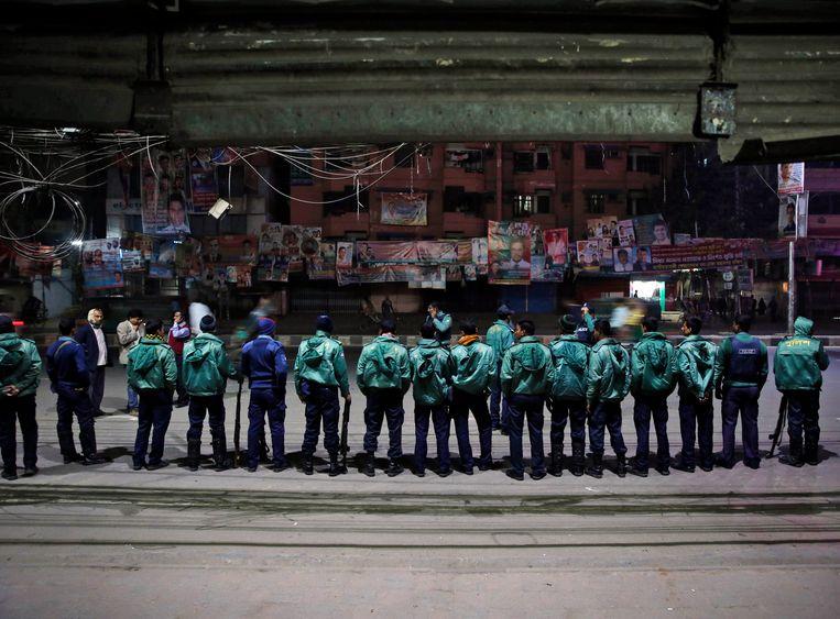 Politie staat op wacht aan het kantoor van de BNP die opriep tot een algemene staking. Beeld AP