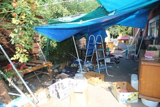 Het terras naast het huis is een jungle van vuilnis en meubels.