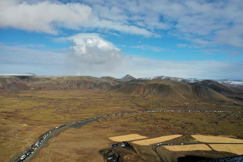 Een kilometerslange slang van blik en rubber kronkelt zich tussen de bergen door naar een verdwijnpunt buiten het kader. Beeld AFP