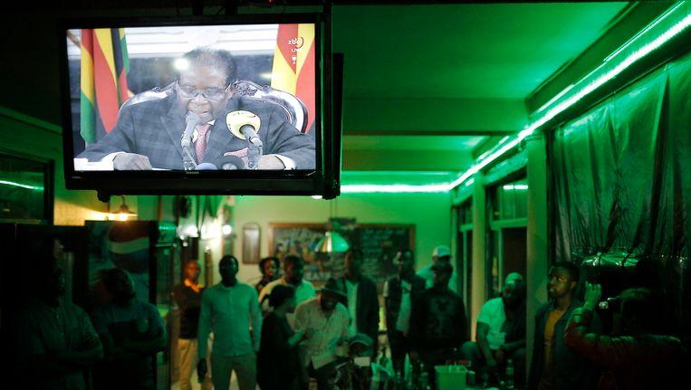 Zimbabwanen kijken naar de televisietoespraak van Mugabe, afgelopen zondag, waarin hij met geen woord repte over zijn vertrek. Beeld epa