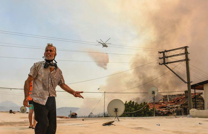 Een inwoner van het dorp Sirtkoy, in de buurt van Manavgat in de provincie Antalya, met op de achtergrond een blushelikopter.