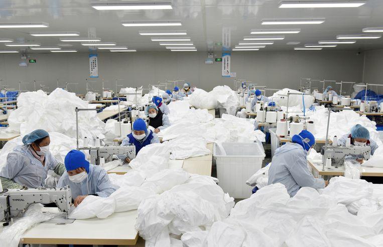 Arbeiders maken in een textielfabriek  in Chaohu, provincie Anhui in China, beschermingspakken voor medisch personeel, foto gemaakt op 28 januari 2020.  Beeld Reuters