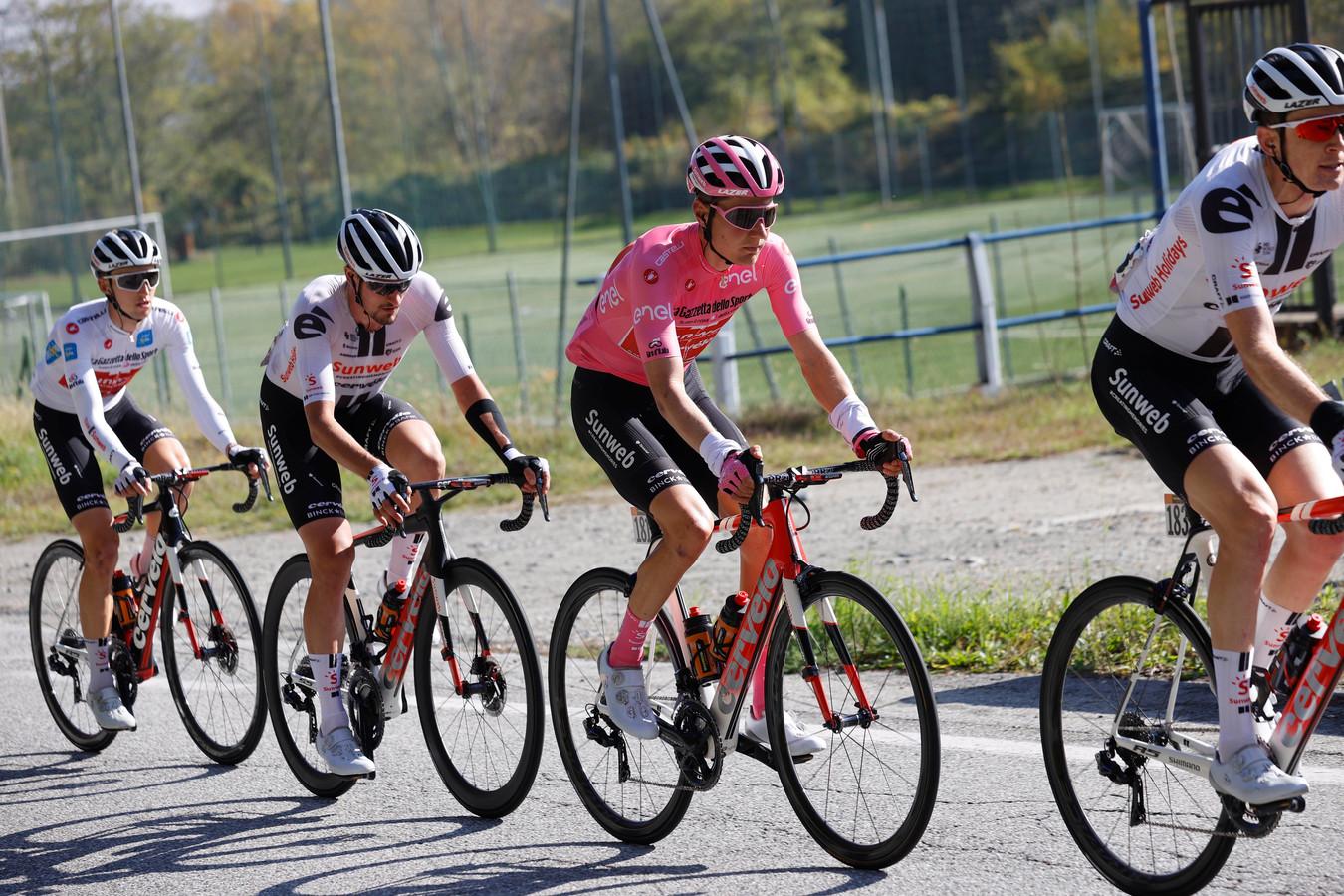 Kelderman in de roze trui, omringd door ploeggenoten.