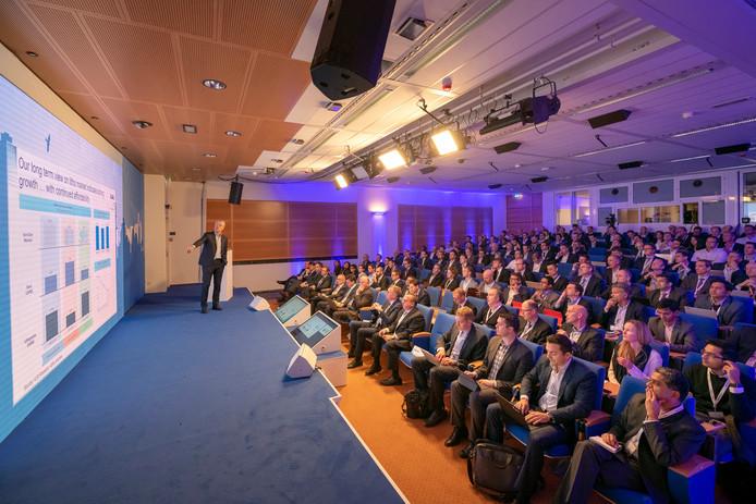 Analisten en beleggers kijken en luisteren bij de uitleg over de toekomstige cijfers bij ASML.