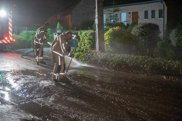 Brandweer ruimt de modder van de weg in de Paulatemstraat.