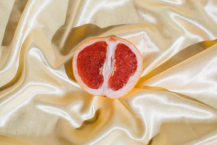 Fresh grapefruit on beige soft silk fabric background. Sex concept. Women's health, sexuality, erotic tension. Female vagina and clitoris symbol. Beeld Getty Images