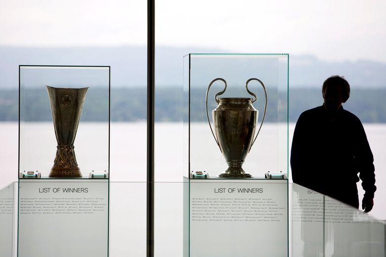 De bekers van de Europa League (l) en de Champions League op het hoofdkwartier van de Eufa in Zwitserland.  Beeld EPA