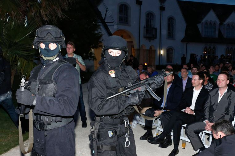 Actors in police costume pose during a mock raid, as Megaupload founder Kim Dotcom (unseen) launches his new file sharing site