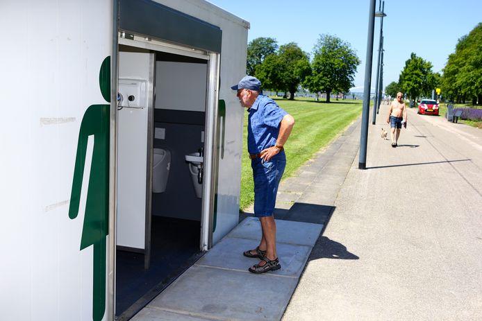 Een voorbijganger werpt een kritische blik naar binnen in het nieuwe openbaar toilet, maar is wel te spreken over het initiatief.