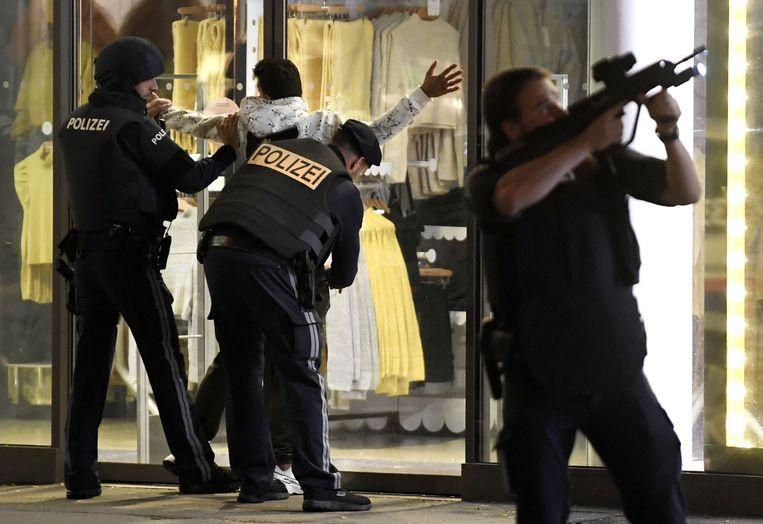 Een voorbijganger wordt kort na de aanslag gefouilleerd in het centrum van Wenen. Beeld AFP