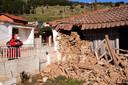 Een man kijkt naar een zwaar beschadigd huis in het Griekse dorp Damassi.