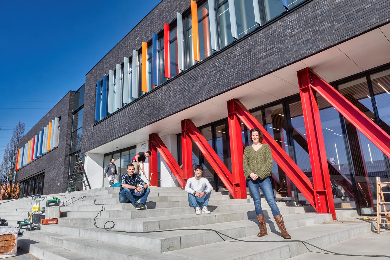 Terwijl het werk aan de nieuwbouw van het Dongemond College nog in volle gang is, poseren docenten die nauw betrokken zijn geweest bij de bouw op de trappen van het gebouw. (vlnr Emiel van den Berg, Levi van Erp en Ilona Leijs).