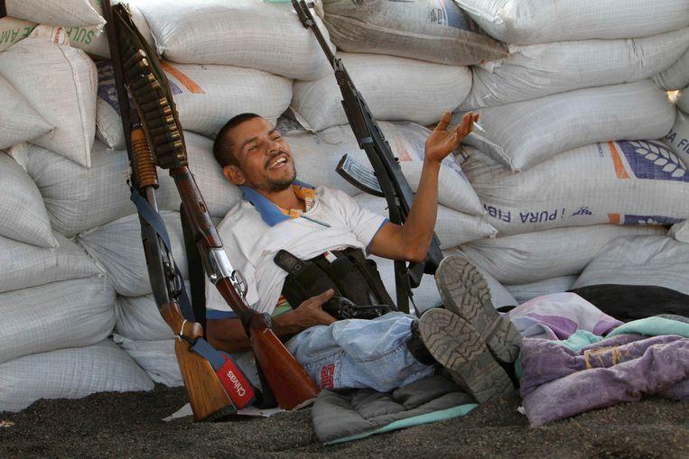 Een zwaarbewapend lid van een burgerwacht zit bij een versperring in de Mexicaanse deelstaat Michoacan. Bij geweld met wapens van Amerikaanse makelij vallen in Mexico tienduizenden doden per jaar.  Beeld Marco Ugarte / AP