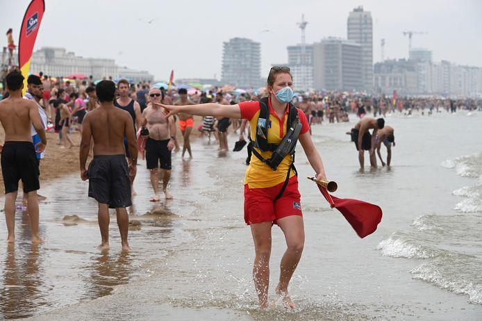 Archief. Een strandredster stuurt badgasten uit het water, omdat er een verloren gelopen kindje gezocht moet worden. De veiligheid in het water kan niet meer gegarandeerd worden.