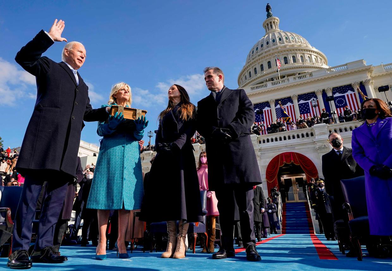 Joe Biden legt de eed af als 46ste president van de VS.Opperrechter John Roberts en vicepresident KamalaHarris (uiterst rechts) kijken goedkeurend toe. Beeld AFP