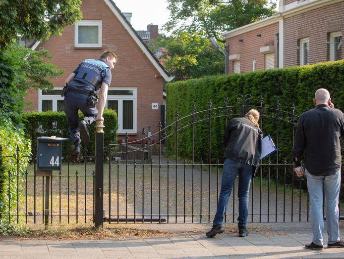Handhavers sluiten de woning aan de Eemnesserweg af.