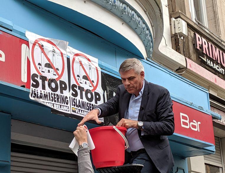 VB-kopstuk Filip Dewinter overplakt Arabische winkelopschriften in Antwerpen als campagnestunt. Beeld BELGAONTHESPOT