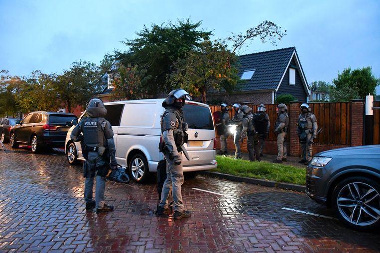 Bij een inval in een woning houdt de politie twee mensen aan.  Beeld Hollandse Hoogte /  ANP