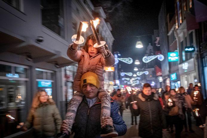 Fakkels voor vrede, enkele honderden mensen trekken op kerstavond door de Heuvelstraat.
