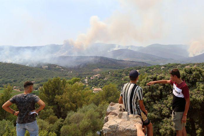La gente guarda gli incendi boschivi a Cogolin (L) e Val de Gilly (R) di Grimaud.