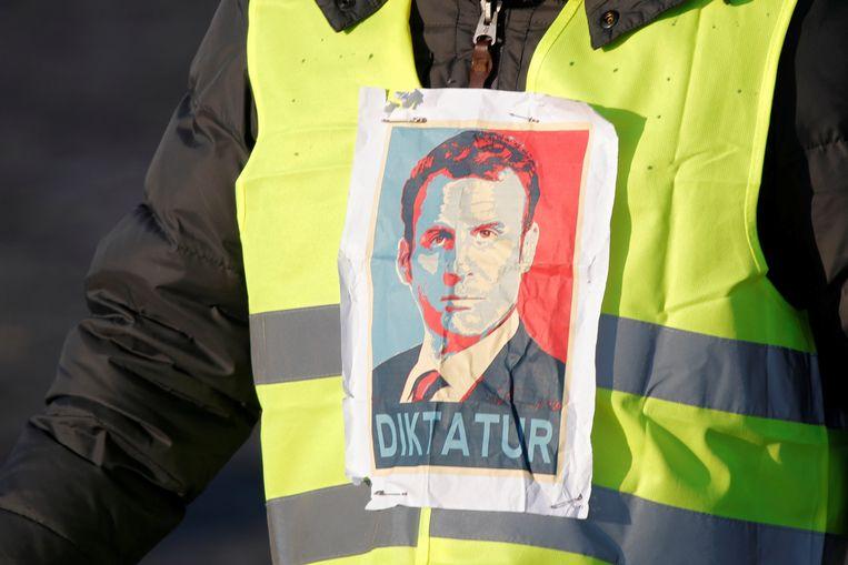 Een geel hesje met afbeelding van Macron. Beeld REUTERS
