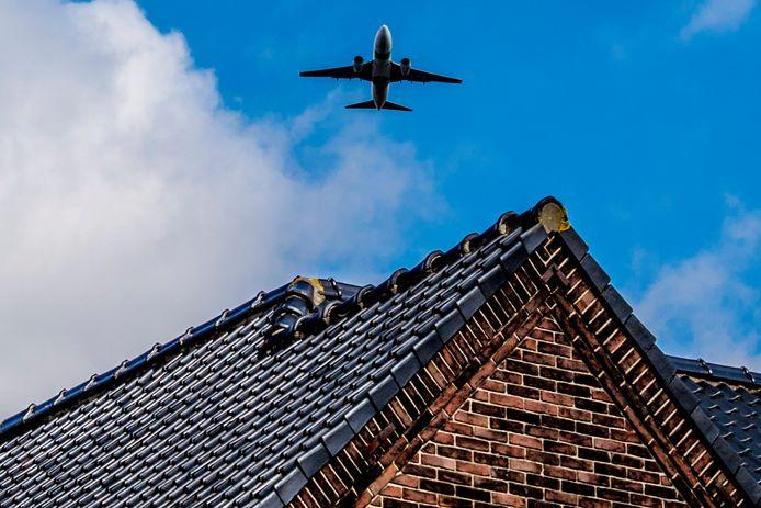 Een vliegtuig vliegt over een huis in de omgeving van Schiphol.