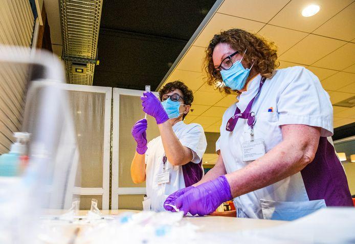 Medewerkers van de ziekenhuisapotheek maken de spuitjes klaar voor het inenten van huisartsen, afgelopen januari.