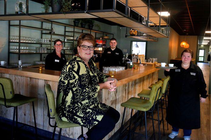Beheerster Greet Hanegraaf zit aan de bar van dorpshuis EMM. Daarachter links begeleidster van Syndion Jiske Bosman en medewerkers Duncan Keizer en Felicia Kelder.