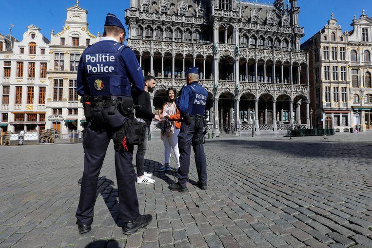 Agenten spreken op de Grote Markt in Brussel mensen aan.  Beeld BELGA