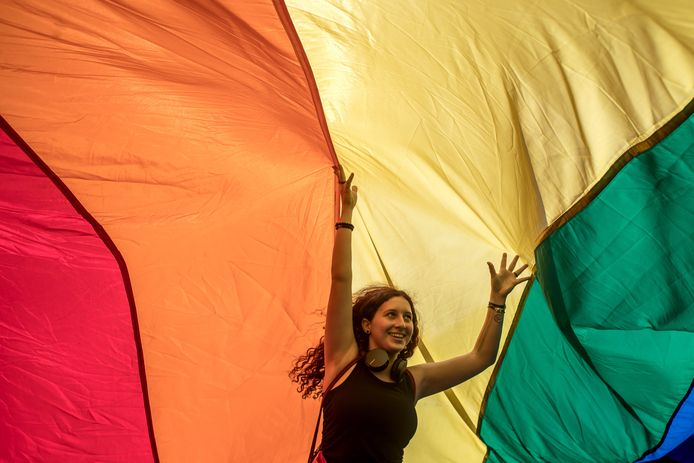 Een vrouw loopt onder een grote regenboogvlag tijdens een Gay Pride Parade in Praag.