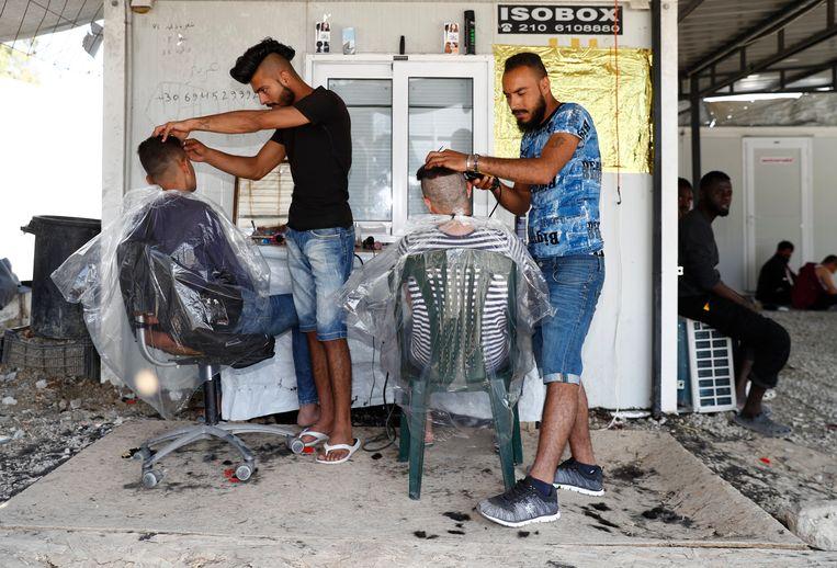 Iraakse vluchtelingen knippen het haar van andere vluchtelingen. Beeld EPA
