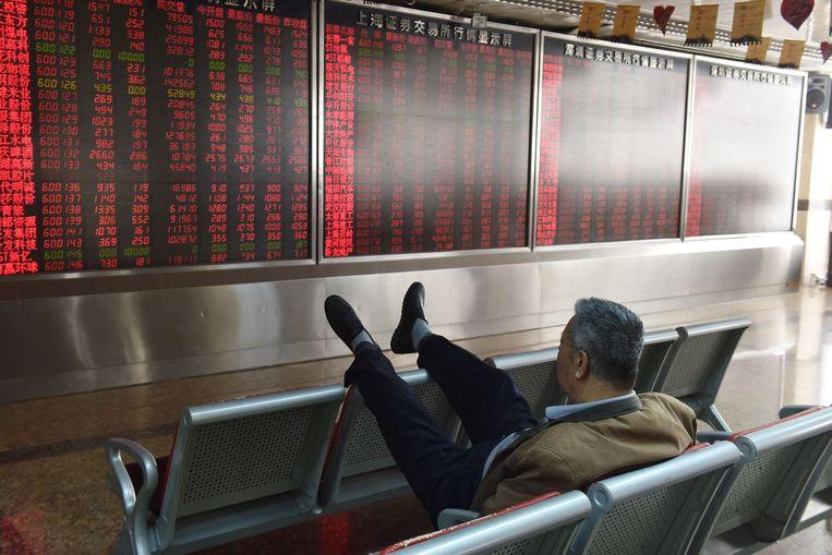 Een belegger houdt de aandelenkoersen in de gaten in Beijing, 19 oktober 2018. Beeld AFP