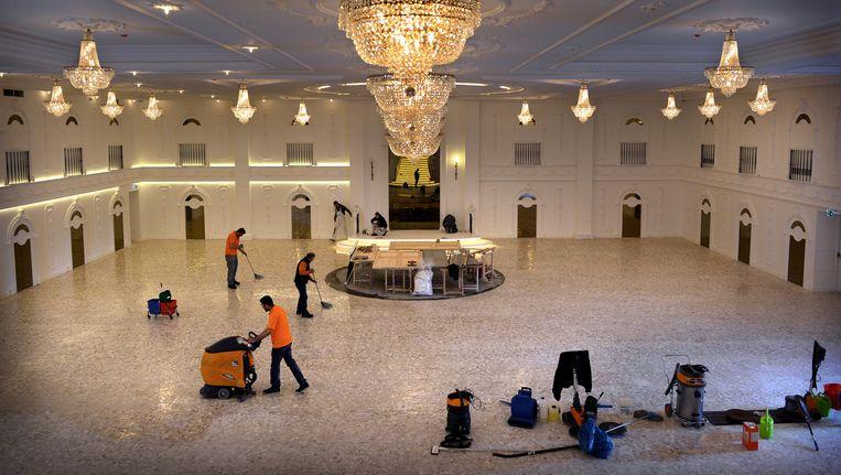 De nieuwe vloer van de grote evenementenlocatie Het Paleis in Schiedam wordt in de was gezet. Gelakte deuren liggen te drogen. Beeld Marcel van den Bergh / de Volkskrant