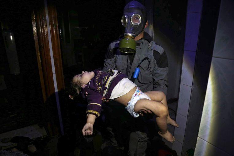 Een reddingswerker draagt een kind dat het slachtoffer zou zijn van de chloorgasaanval op de stad Douma. Beeld AP
