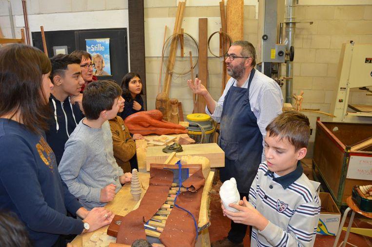 Leerkracht Kris Waelput vertelt de kinderen over het ambacht van de houtsnijder.