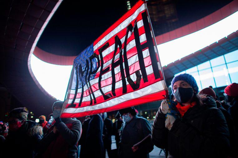 Demonstranten houden een banner vast waarmee ze oproepen tot het afzetten van President Donald Trump. Beeld AFP