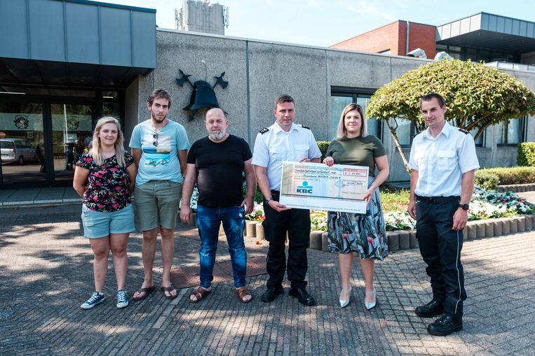 In de brandweerkazerne van Heusden overhandigen enkele mensen een cheque met geld voor de families van de overleden en gewonde brandweermannen.